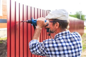 45454857 - build a metal fence. an elderly man with a drill builds metal fence